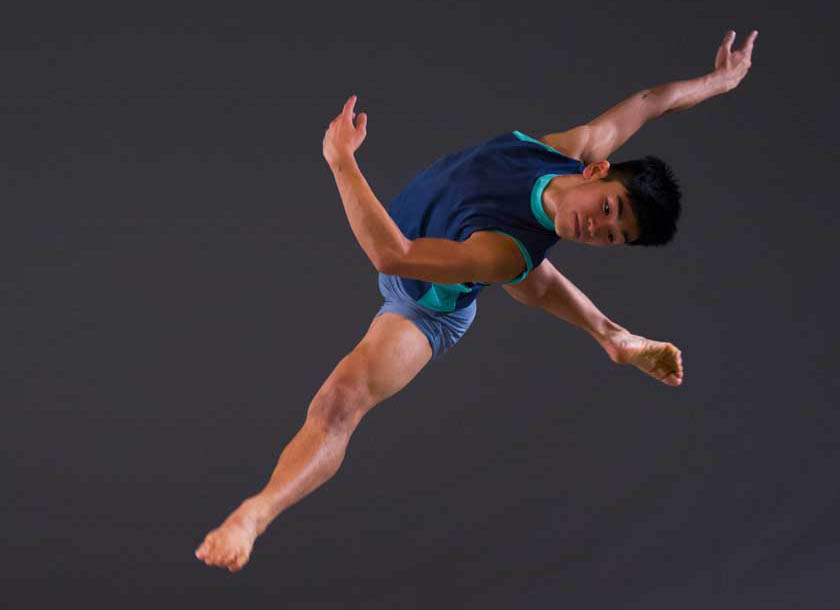 Male dancer in air wearing blue