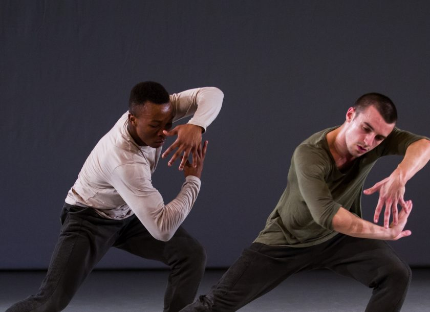Two male dancers in green and grey