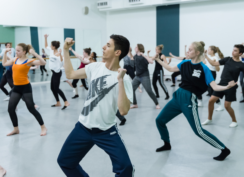 In class photo of many dancers rehearsing