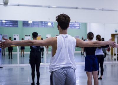 Male dancer with arms outstretched in contemporary dance class