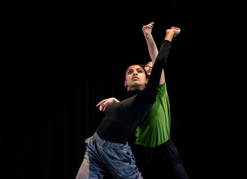 Rambert Grades two dancers wearing black and green reaching