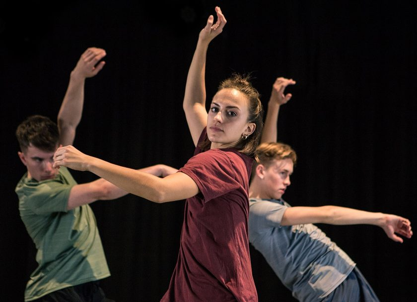 hree contemporary dancers learning Rambert Grades, wearing red blue and green, one girl two boys.