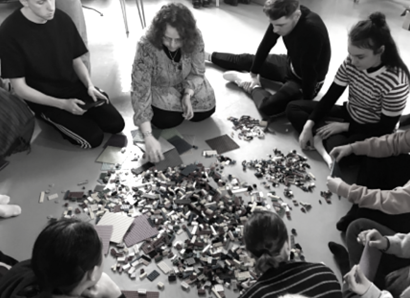 Group gathered around Lego blocks sitting on the floor.