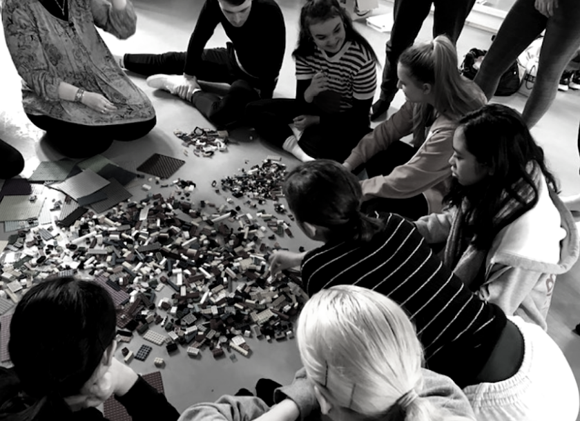 Group sitting around Lego blocks on the floor