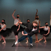 Choreographer Cameron McMillan in front of group of dancers in black tutus